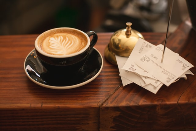 A latte with a foam design sitting on a counter next to cafe order receipts